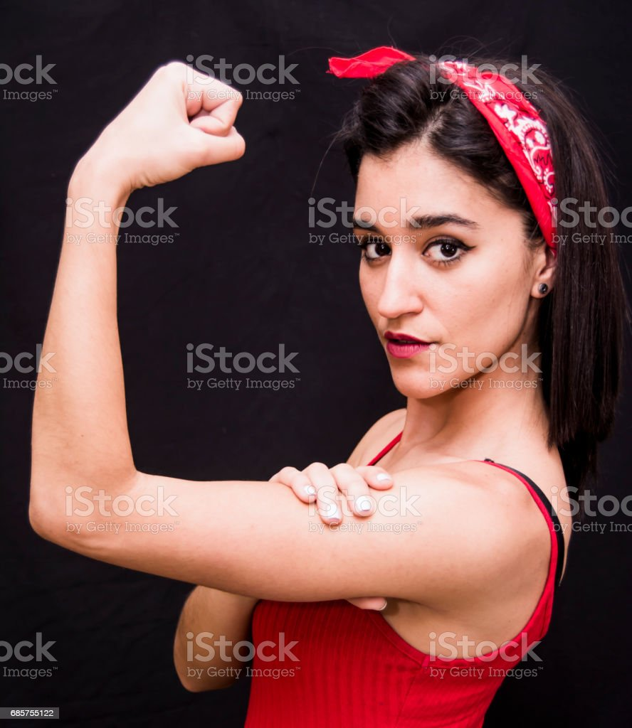 Portrait of a beautiful woman  with red scarf on her head making a gesture of strength on her arms royalty free stockfoto