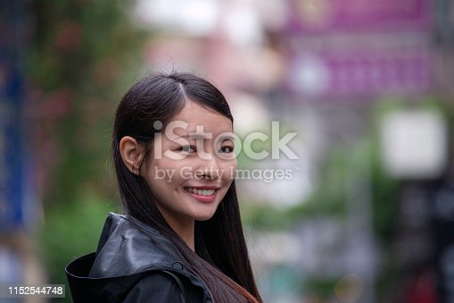 istock Portrait of a beautiful young Asian woman smiling at the street 1152544748