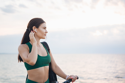 Portrait of a beautiful young brunette woman resting after bicycle ride at sunrise listening to music with wireless earbuds.