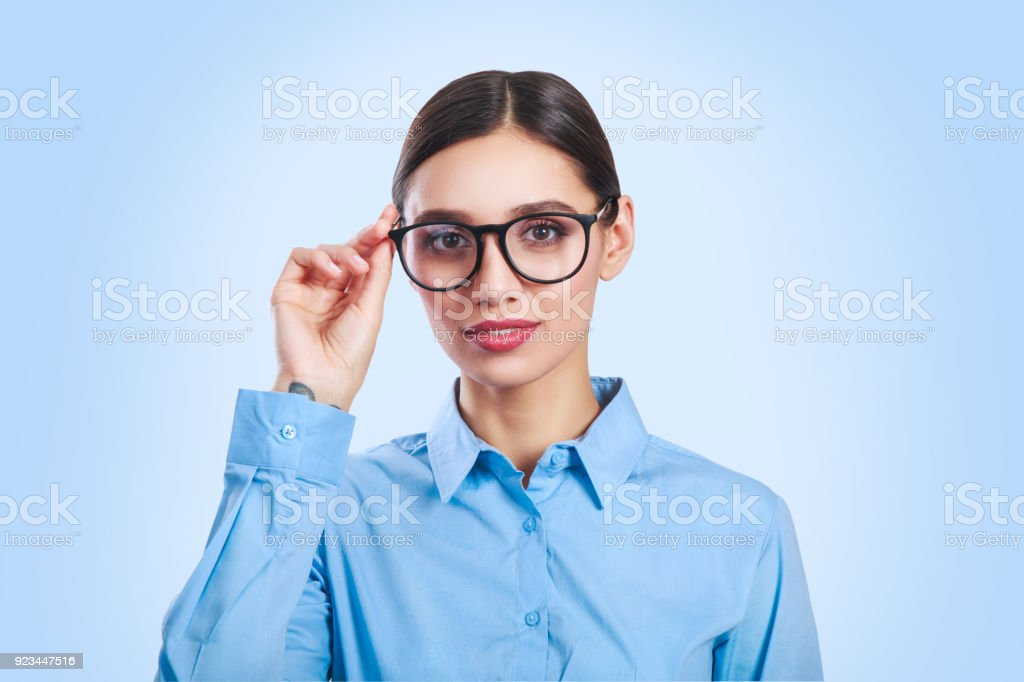 Portrait of a beautiful young business woman standing against blue background stock photo