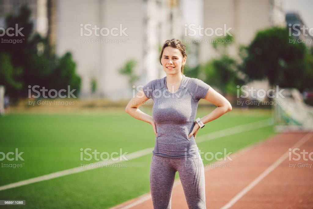 Portrait of a beautiful young caucasian woman with long hair in the tail and big breasts posing in gray sportswear standing training on a running stadium, a red rubber track in summer on a sunny day stock photo