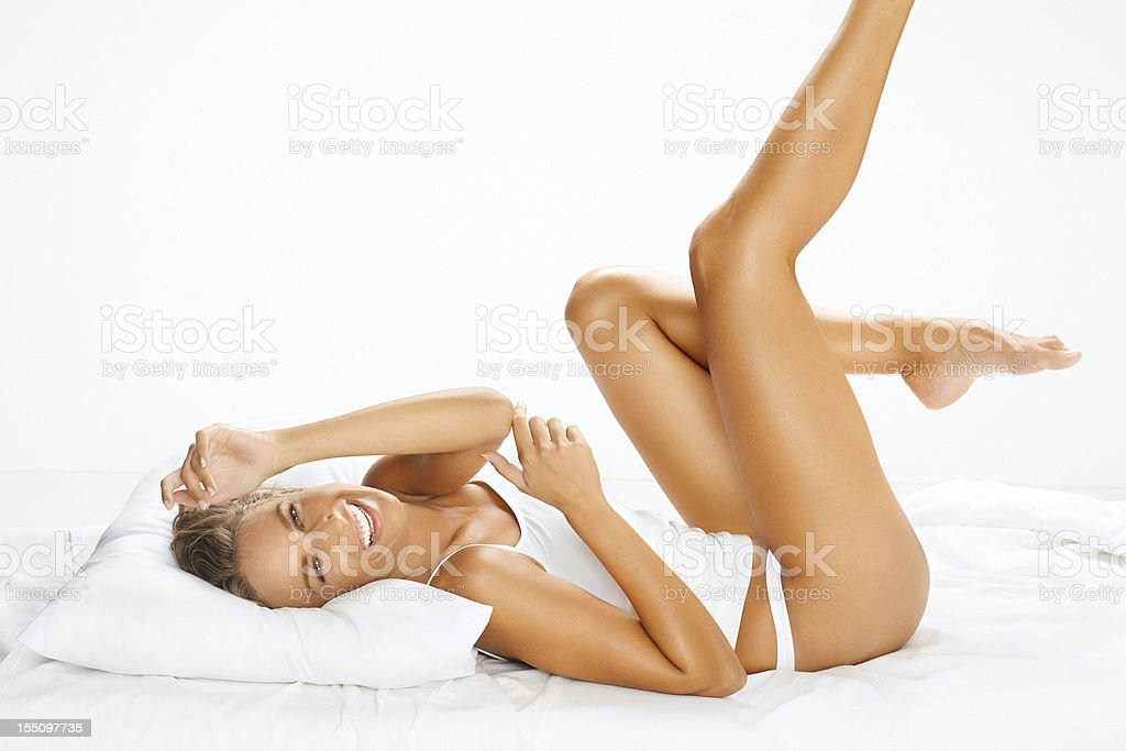 Portrait of a beautiful, young, cheerful woman relaxing on bed royalty-free stock photo