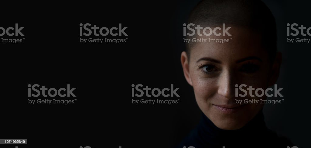 Portrait of a beautiful young courageous smiling female cancer patient, with shaved head. Gorgeous woman, a cancer patient, portrait on dark background with copy space. stock photo