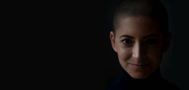 Portrait of a beautiful young courageous smiling female cancer patient, with shaved head. Gorgeous woman, a cancer patient, portrait on dark background with copy space. Portrait of a beautiful young courageous smiling female cancer patient, with shaved head. Gorgeous woman, a cancer patient, portrait on dark background with copy space. shaved head stock pictures, royalty-free photos & images