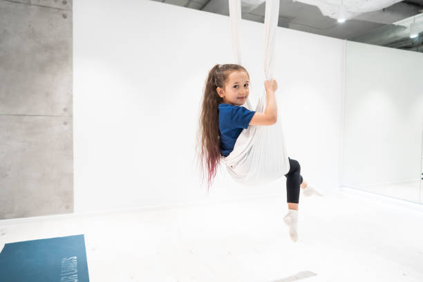 portrait of a beautiful young girl engaged in fly yoga on canvases. stock photo