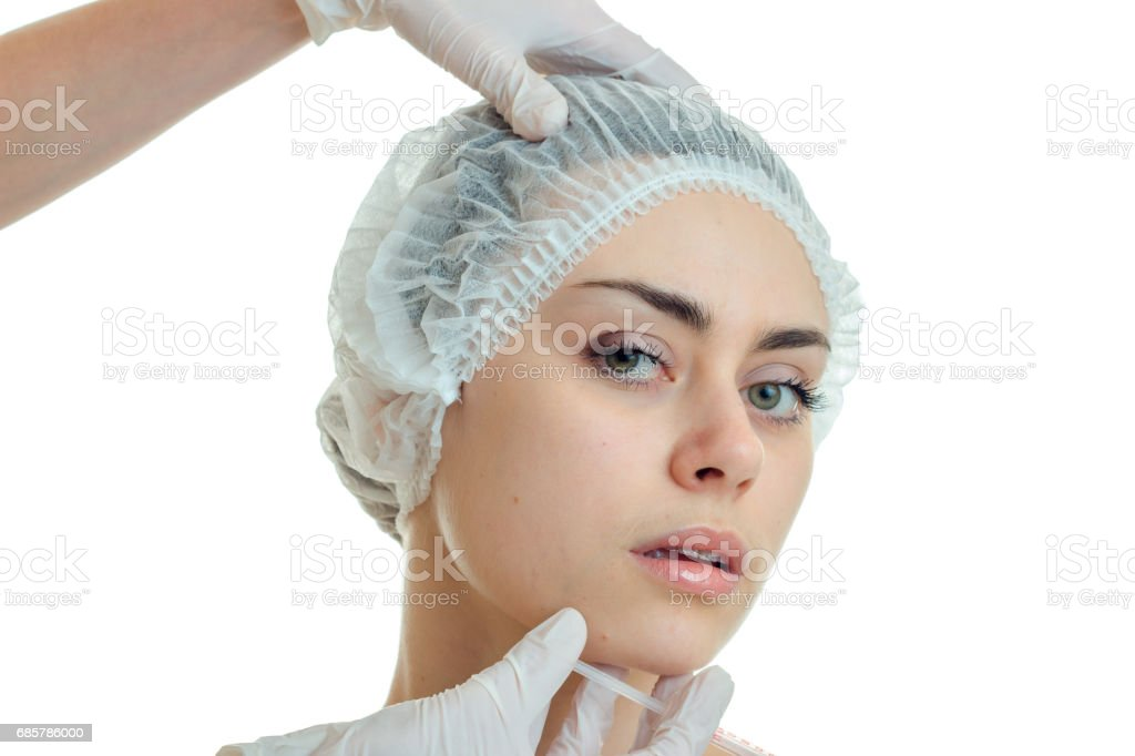 Portrait of a beautiful young girl in medical hair hat that looks into the camera close-up royalty-free stock photo