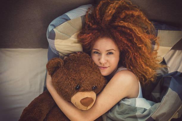 Porträt eines schönen jungen Mädchens mit Teddybär schlafen im Bett zu Hause – Foto