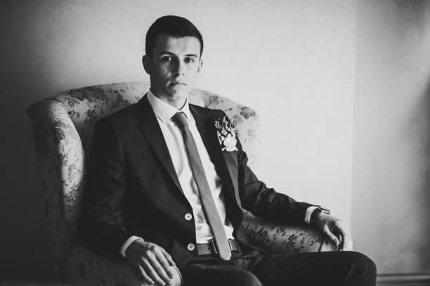 porträt einer schönen jungen bräutigam auf retro-sessel. zarte emotion auf dem gesicht. schwarz / weiß foto. - bräutigam anzug vintage stock-fotos und bilder