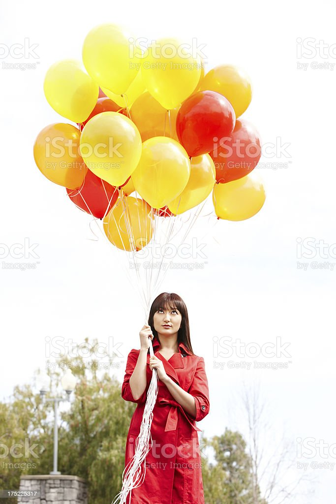 Portrait of a beautiful young Japanese woman holding balloons royalty-free stock photo