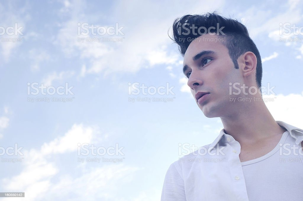 Portrait of a beautiful young male modelon sky background royalty-free stock photo