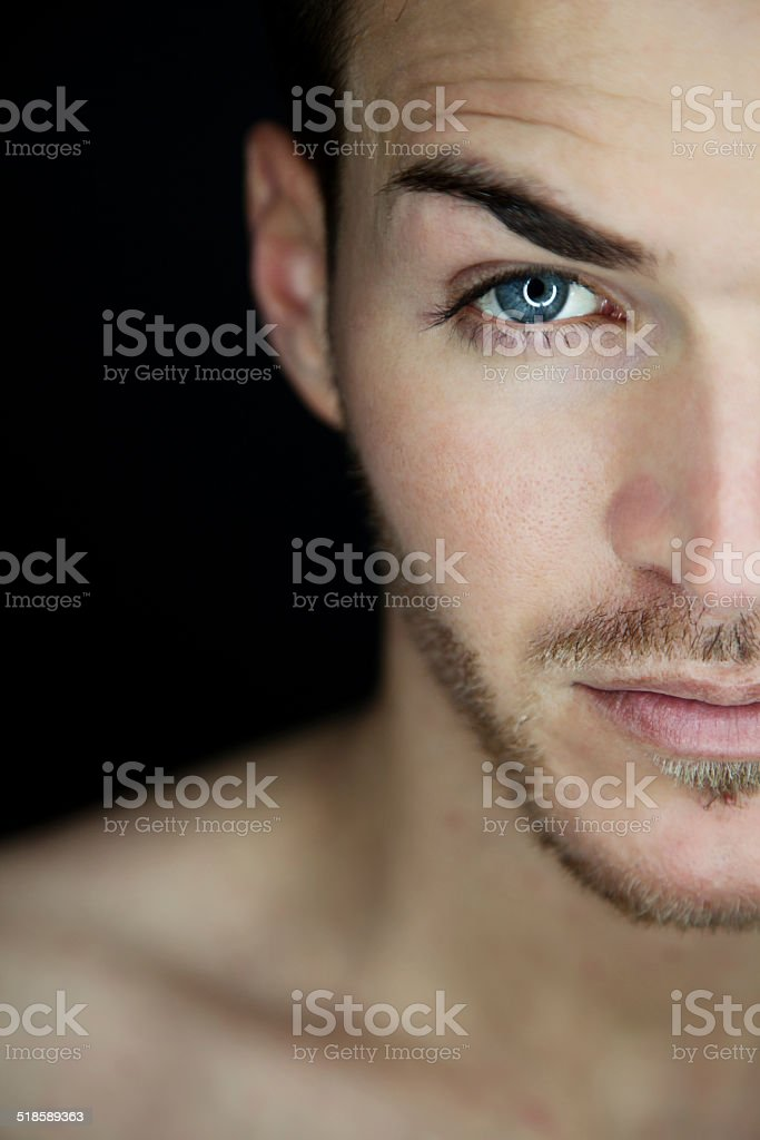 Portrait of a beautiful young man half face stock photo