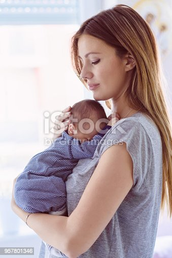 Happy beautiful mom holding an infant