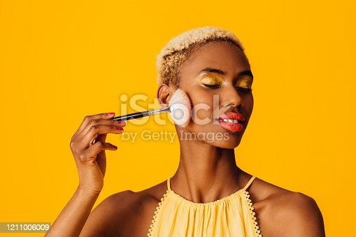 498422806 istock photo Portrait of a beautiful young woman applying cover up loose powder  to her cheeks with a makeup brush, eyes closed 1211006009
