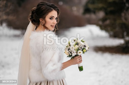 Portrait of a beautiful bride in a winter forest. Woman in a wedding dress, in a white fur coat and with a bouquet in hands