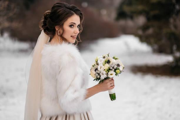 porträt einer schönen jungen frau, braut, in einen winterwald - brautstrauß aus holz stock-fotos und bilder