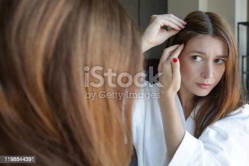 1130731761 istock photo Portrait of a beautiful young woman examining her scalp and hair in front of the mirror, hair roots, color, grey hair, hair loss or dry scalp problem 1198844391
