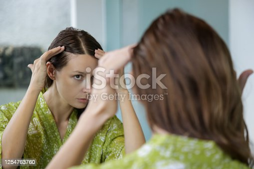 1130731761 istock photo Portrait of a beautiful young woman examining her scalp and hair in front of the mirror, hair roots, color, grey hair, hair loss or dry scalp problem 1254763760
