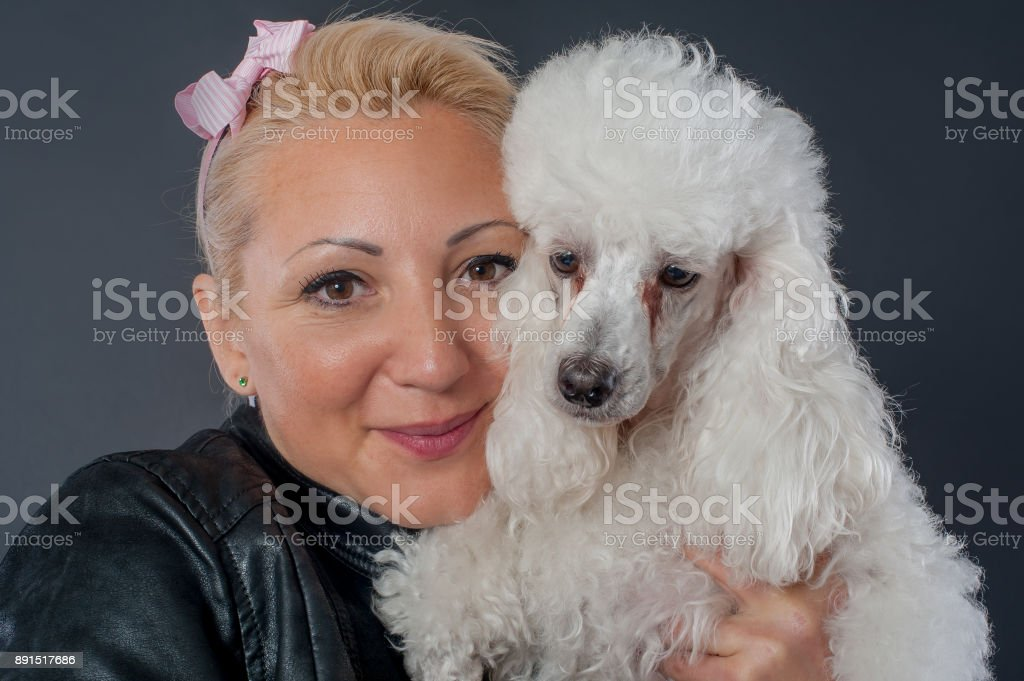 Portrait of a beautiful young woman hugging her beautiful dog stock photo
