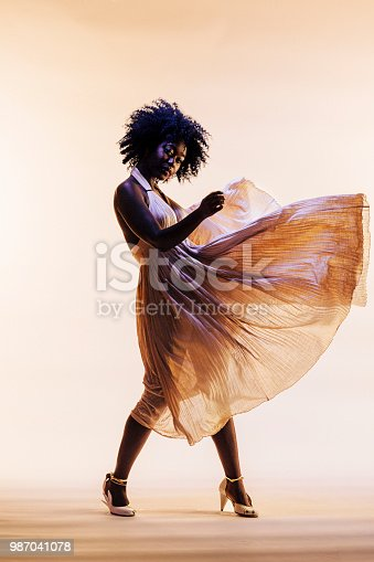 Portrait of a beautiful young woman in an elegant fancy dress that seems to float in the air, isolated on a studio background