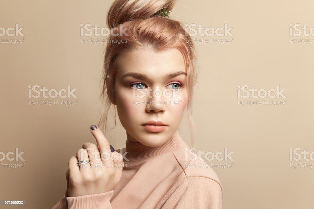 Portrait of a beautiful young woman in soft powdery beige pastel colors with natural make-up стоковое фото