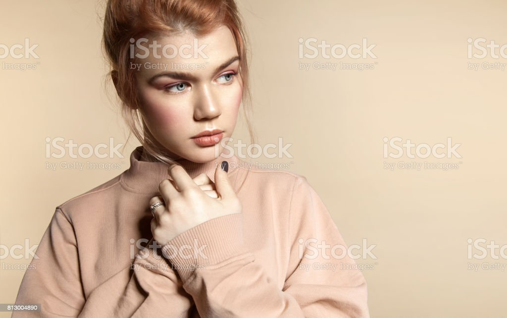 Portrait of a beautiful young woman in soft powdery beige pastel colors with natural make-up in a peach sweatshirt on a beige background стоковое фото