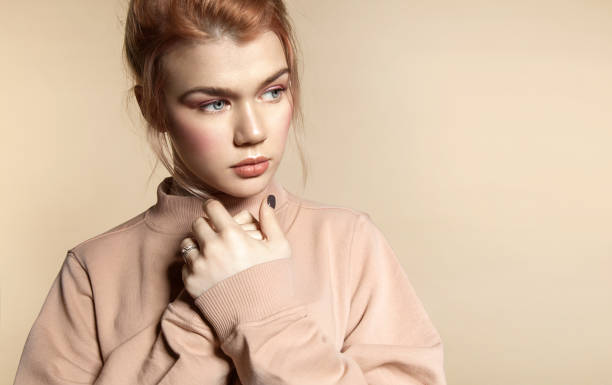 Cтоковое фото Portrait of a beautiful young woman in soft powdery beige pastel colors with natural make-up in a peach sweatshirt on a beige background