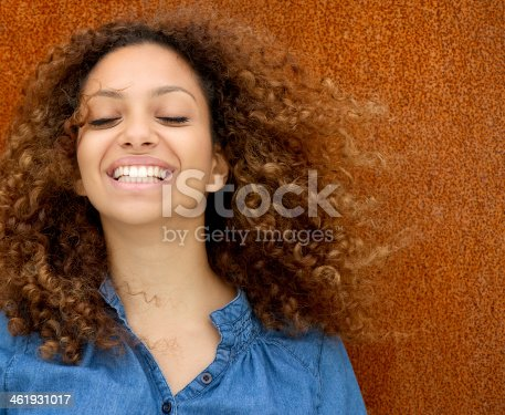 186534921 istock photo Portrait of a beautiful young woman laughing with curly hair 461931017