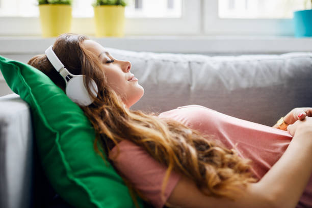 portrait of a beautiful young woman lying on sofa with headphones on and closed eyes, relaxing - listening stock pictures, royalty-free photos & images