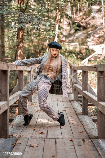 Portrait of a beautiful young fashionable woman posing on a wooden bridge in nature on a sunny autumn day. She is wearing a beret.