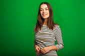 Portrait of a young woman looking at the camera while clasping her hands. She is standing in front of a green studio background.