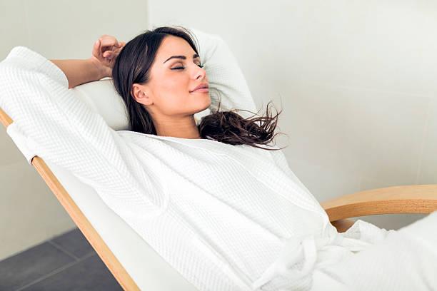 ritratto di una bellissima giovane donna rilassante in accappatoio - accappatoio foto e immagini stock