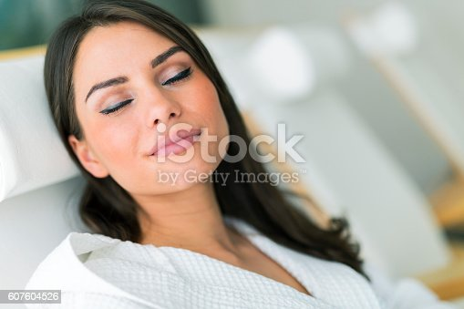 610769340istockphoto Portrait of a beautiful young woman relaxing in a robe 607604526