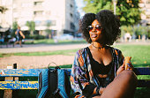 Vintage toned portrait image of a beautiful African American woman, sitting in a city park in Belgrade, Eastern Europe, relaxing, listening to music, having an easy afternoon.