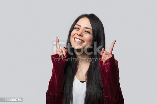 610678842 istock photo Portrait of a beautiful young woman smiling over gray background. 1199958783