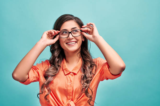 Portrait of a beautiful young woman wearing an orange shirt and glasses stands on a blue background and looks up.Copy space. stock photo
