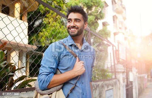 Portrait of a beautifull smiling man indian ethnicity looking at the camera.He is wearing navy blue shirt and holding bag over the shoulder