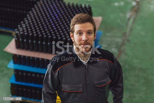Happy beer maker looking at camera.