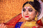 Portrait of a Bengali bride or Indian bride in traditional wedding sari or saree and heavy gold jewelry