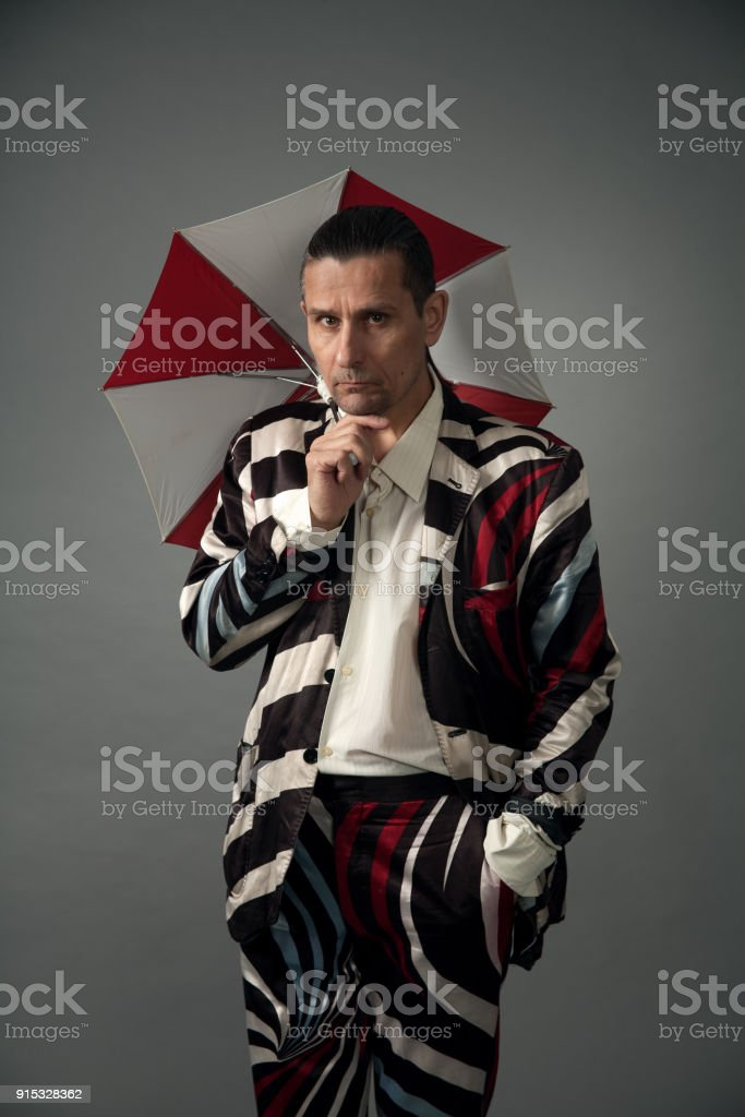Portrait of a bizarre man in a suit in a studio on a gray background stock photo
