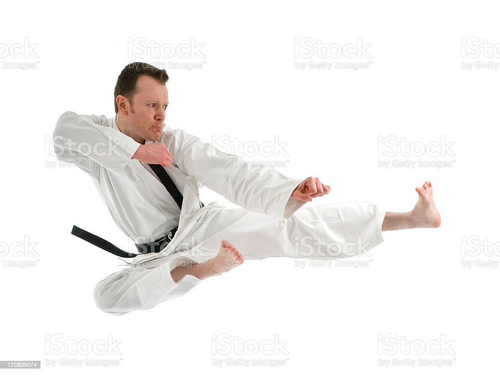 Portrait of a black belt man doing a high kick on white stock photo