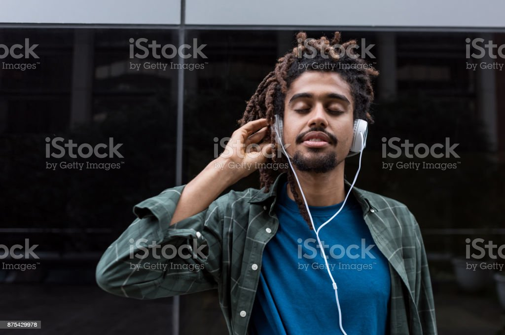 Portrait of a latin american black man listening music with...
