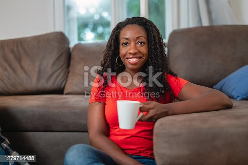 Portrait of a happy black woman in her 30's drinking coffee and looking at camera