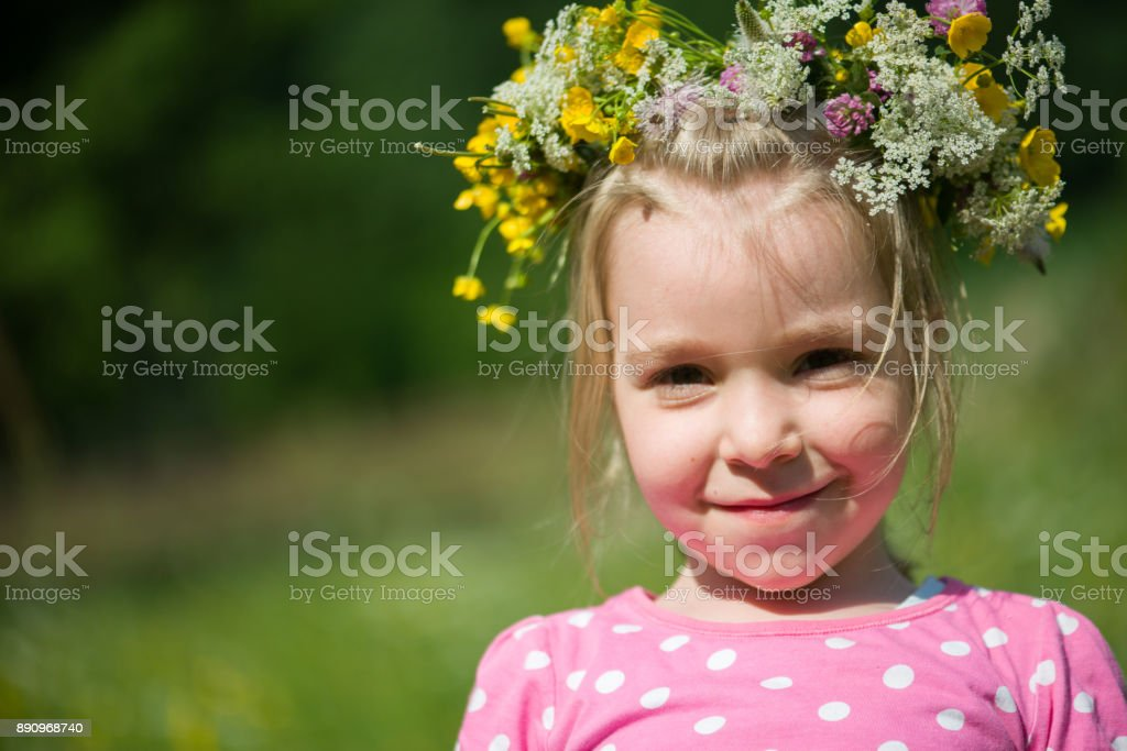 Portrait of a blonde little girl with a wreath of flowers on her head stock photo