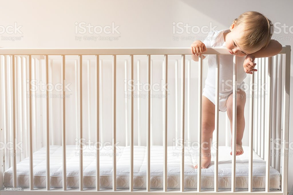 Portrait of a bored baby standing in a crib. stock photo
