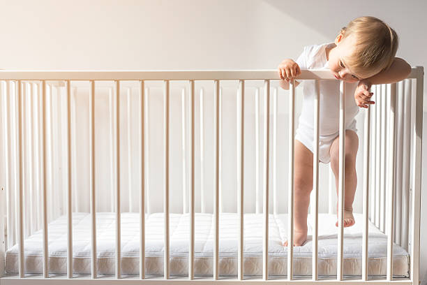 portrait of a bored baby standing in a crib. - playpen stock pictures, royalty-free photos & images