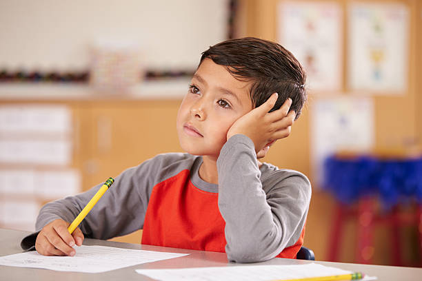 Portrait of a boy daydreaming in an elementary school class stock photo