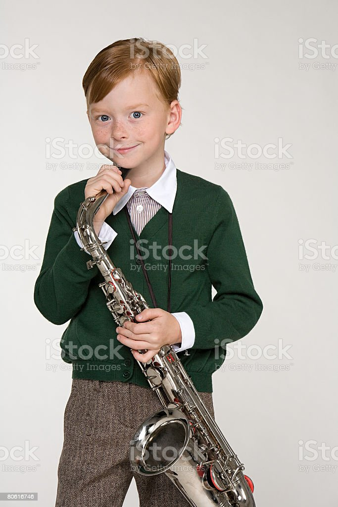 A portrait of a boy holding a saxophone stock photo