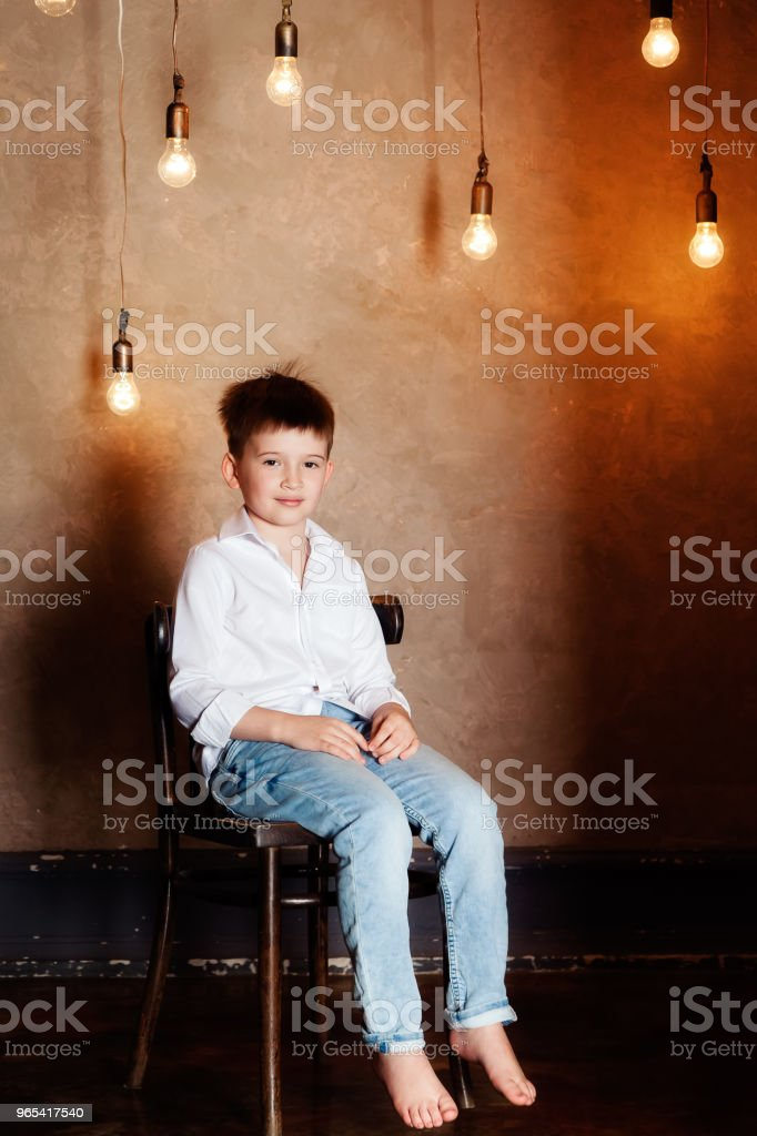 Portrait of a boy sitting among light bulbs zbiór zdjęć royalty-free
