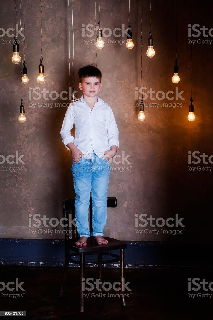 Portrait of a boy standing among light bulbs zbiór zdjęć royalty-free