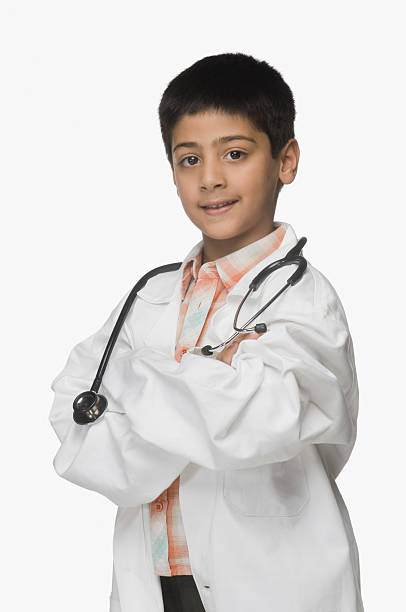 Portrait of a boy wearing lab coat and holding a stethoscope stock photo
